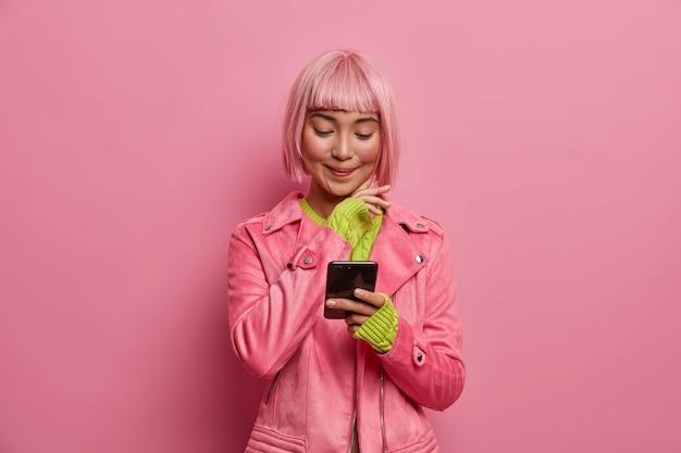 Zufriedene charmante frau social media blogger mit stilvoller frisur, hält smartphone, liest artikel im internet