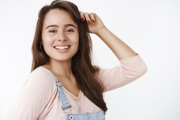 Zufriedene, charmante, freundlich aussehende, attraktive weibliche brünette, die mit haaren spielt, lacht und lächelt, als sie auf der linken seite steht und positive freudige emotionen über grauer wand ausdrückt. platz kopieren