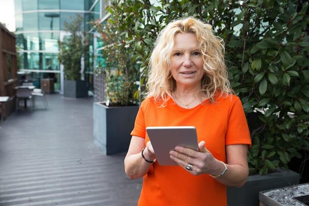 Zufriedene dame beim surfen im internet auf der außenterrasse