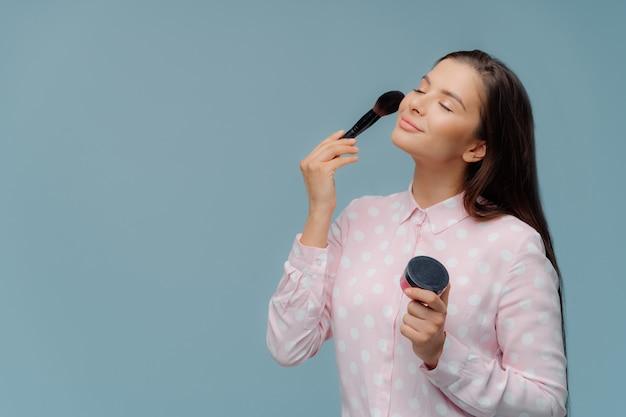 Zufriedene dame trägt grundierung mit kosmetikpinsel auf