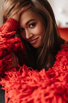 Zufriedene dunkelhaarige frau lächelt, beugt sich vor und hüllt sich in eine rote strickjacke.