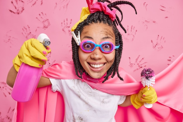 Zufriedene dunkelhäutige frau, die wie superhelden gekleidet ist, sprüht waschmittel hält toilettenbürste trägt schutzbrille umhang schätzt sauberkeit lächelt glücklich isoliert über rosa wand