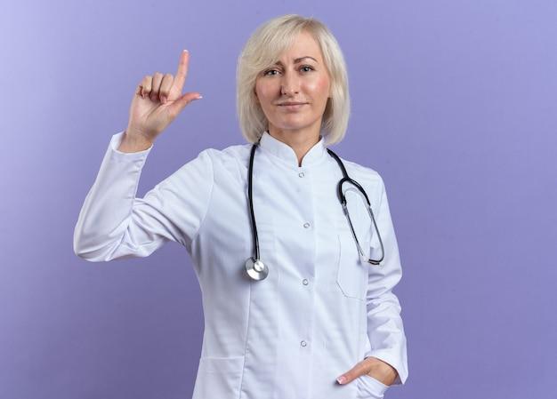 Zufriedene erwachsene ärztin im medizinischen gewand mit stethoskop nach oben isoliert auf lila wand mit kopierraum