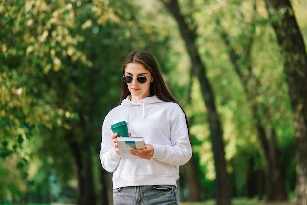Zufriedene erwachsene frau, die im sommer eine kaffeetasse im park hält