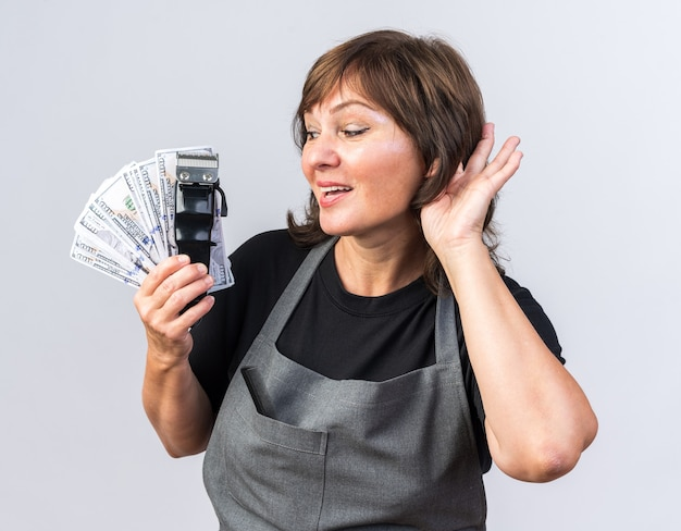 Zufriedene erwachsene friseurin in uniform, die haarschneidemaschine mit geld hält und die hand nahe am ohr hält und versucht, isoliert auf weißer wand mit kopierraum zu hören?