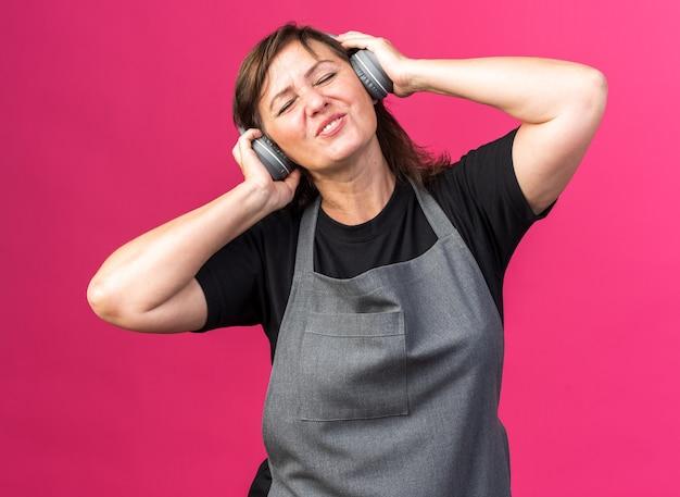 Zufriedene erwachsene friseurin in uniform mit kopfhörern isoliert auf rosa wand mit kopierraum