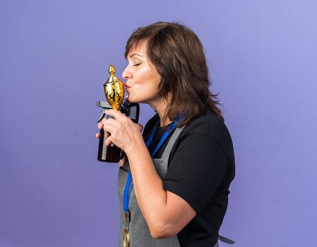 Zufriedene erwachsene weibliche friseurin in uniform mit goldener medaille um den hals, die haarschneidemaschine und sprühflasche küssen, die siegerpokal einzeln auf lila wand mit kopienraum küssen