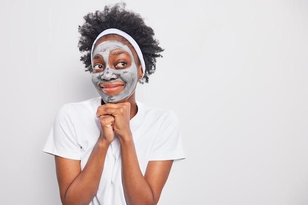 Zufriedene ethnische frau mit lockigem haar hält die hände unter dem kinn und lächelt angenehm weg sieht eine tonmaske auf, kümmert sich um den teint