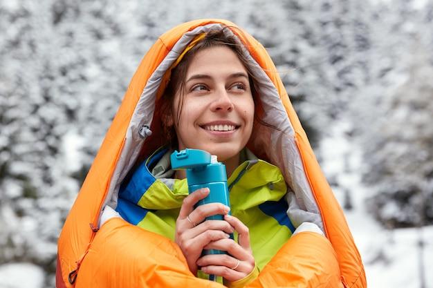 Zufriedene europäische frau trägt badetasche, reist in schneebedeckten bergen, hält flasche mit heißem getränk