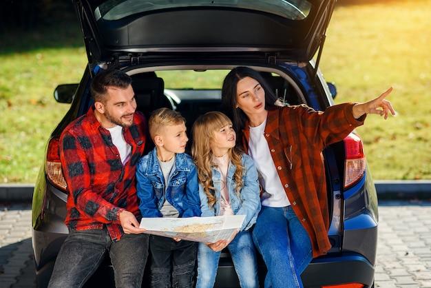 Zufriedene familie aus hübschem vater, hübscher mutter und schönen kindern, die auf der straßenkarte schauen, während sie im kofferraum des autos sitzen.