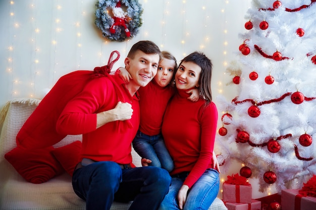 Zufriedene familie im rot, das an der kamera aufwirft
