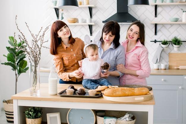 Zufriedene familie mit großmutter, zwei töchtern und kleinem mädchen, die zeitvertreib an ostern genießen und cupcakes essen. ein kleines mädchen hat hasenohren auf dem kopf.