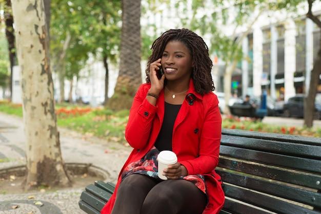 Zufriedene frau, die auf bank sitzt und telefonisch spricht