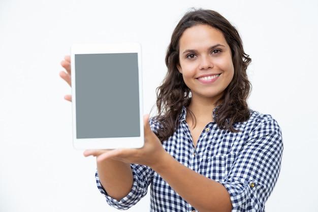 Zufriedene frau, die digitale tablette zeigt
