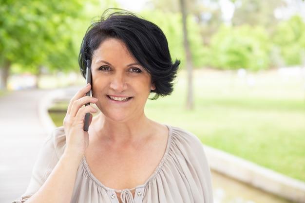 Zufriedene frau, die draußen durch smartphone spricht