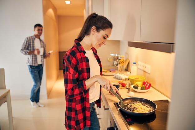 Zufriedene frau, die ein omelett auf dem induktionskochfeld zubereitet