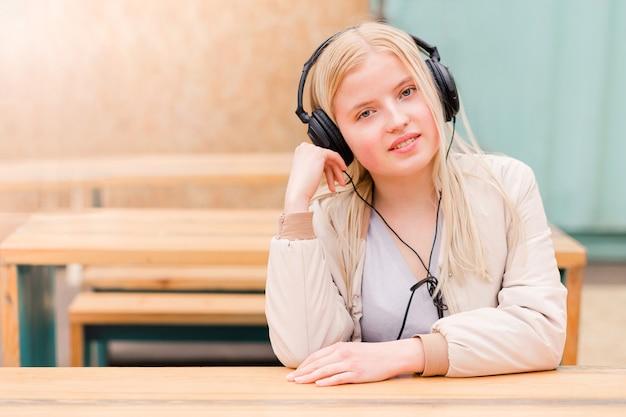 Zufriedene frau, die frische luft atmet und musik über kopfhörer hört