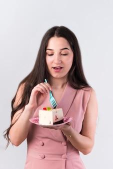 Zufriedene frau, die geburtstagskuchen isst