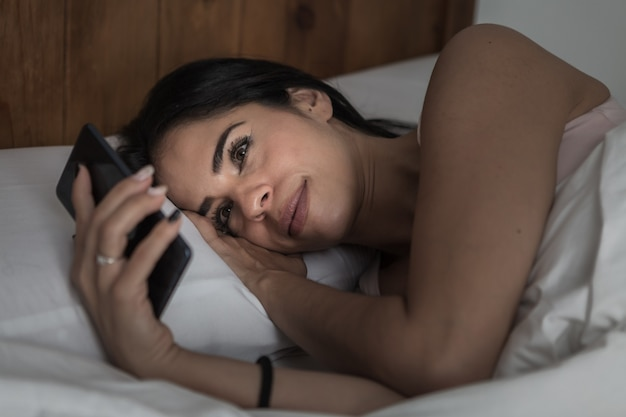 Zufriedene frau, die im bett liegt und smartphone durchsucht
