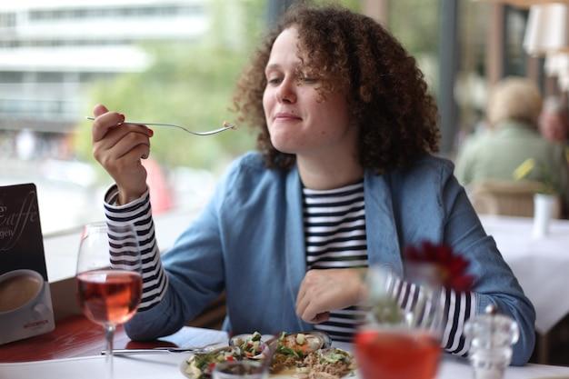 Zufriedene frau, die köstlichen salat im restaurant isst