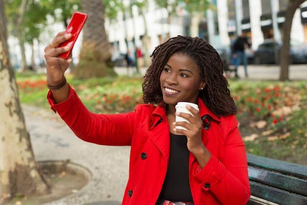 Zufriedene frau, die selfie mit smartphone auf straße nimmt