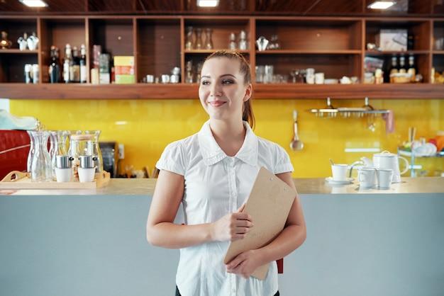 Zufriedene frau mit dem klemmbrett, das kaffeestubegeschäft handhabt