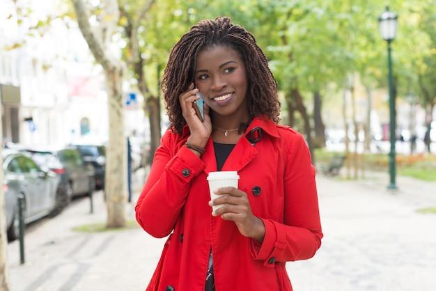 Zufriedene frau mit papierschale sprechend durch smartphone