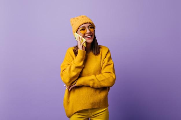 Zufriedene frau mit schulterlangen haaren glücklich beim gespräch mit bester freundin per smartphone. aufrichtig lächelnder student in stilvollem hut und gelbem outfit will schnappschuss auf isoliertem purpur machen