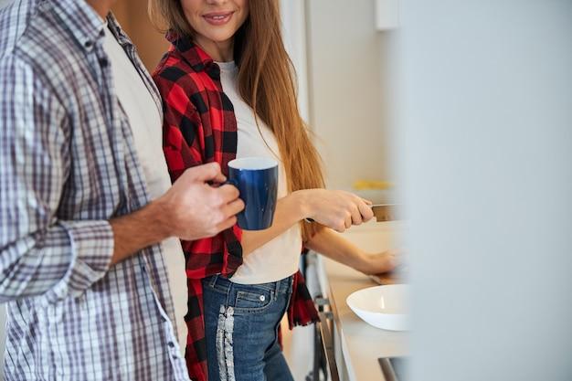 Zufriedene frau und ein mann an der küchentheke