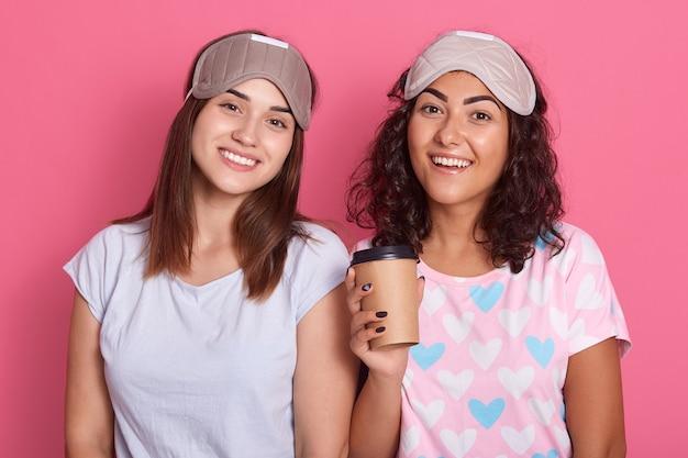 Zufriedene frauen posieren isoliert über rosenhintergrund, tragen pyjamas und schlafmasken, haben gute laune, lächeln in die kamera, drücken positiv aus, wachen nach pyjama-party auf.