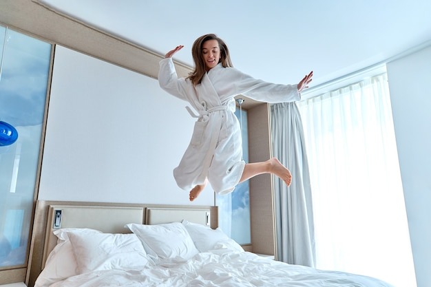 Zufriedene freudige lustige frau im bademantel, die während eines glücklichen moments auf das bett in einem hotelzimmer springt. wohlfühlen und lebenskonzept genießen. einfacher lebensstil