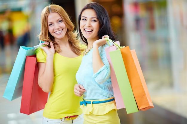 Zufriedene freunde mit ihren shopping-tag
