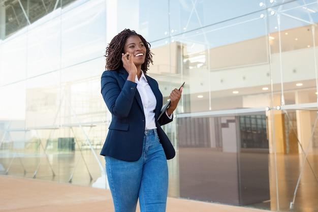 Zufriedene geschäftsfrau, die durch smartphone geht und spricht