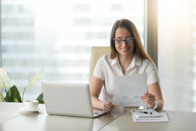 Zufriedene geschäftsfrau, die finanzergebnisse revidiert