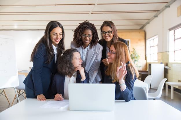Zufriedene geschäftsfrauen, die mit laptop arbeiten