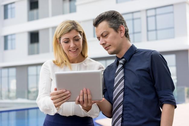 Zufriedene geschäftsleute, die draußen nachrichten auf tablet-computer lesen.