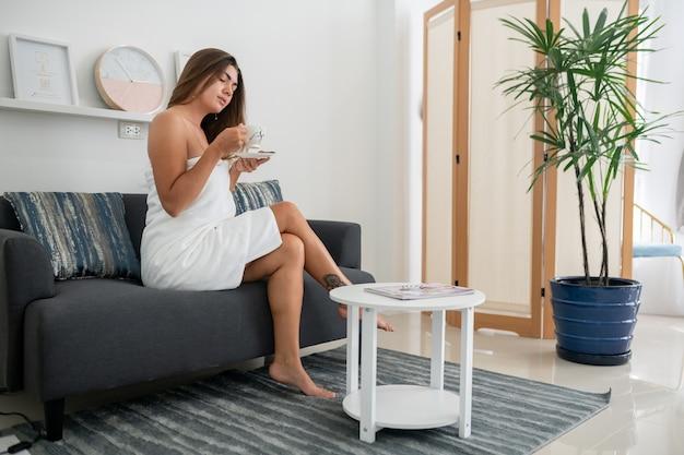 Zufriedene gesunde europäische frau, eingewickelt in weiße weiche handtücher, hält eine tasse tee und entspannt sich nach der spa-behandlung