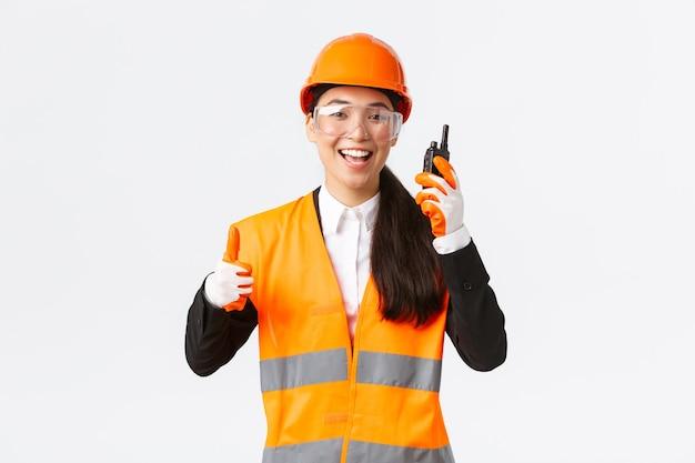 Zufriedene, glücklich lächelnde asiatische ingenieurin, industrietechnikerin in schutzhelm und uniform, die daumen hoch zeigt, während sie großartige arbeit mit walkie-talkie lobt, die erlaubnis zur arbeit geben