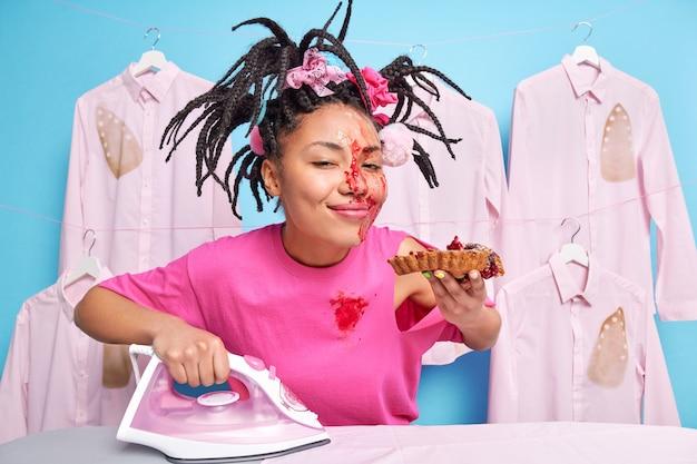 Zufriedene haushälterin genießt es, köstlichen gebackenen kuchen zu essen, hat schmutziges gesicht