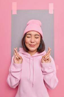 Zufriedene hoffnungsvolle junge asiatin drückt die daumen, glaubt an viel glück erwartet für einige ergebnisse, schließt die augen, gekleidet in rosa bequemen hoodie und hut posiert gegen leere leere wand