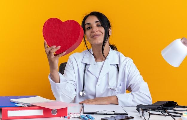 Zufriedene junge ärztin, die ein medizinisches gewand mit stethoskop trägt, sitzt am tisch mit medizinischen instrumenten, die eine herzförmige box isoliert auf gelber wand halten