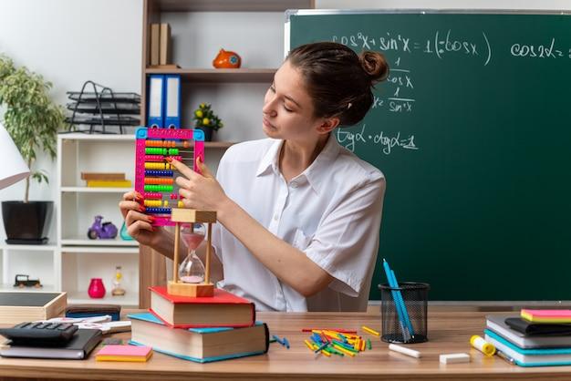 Zufriedene junge blonde mathematiklehrerin, die am schreibtisch mit schulwerkzeugen sitzt und mit dem finger auf den abakus im klassenzimmer schaut und zeigt