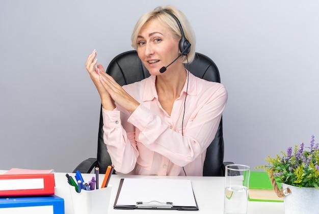Zufriedene junge callcenter-betreiberin mit headset am tisch sitzend mit bürowerkzeugen, die die hände zusammenhalten, isoliert auf weißer wand
