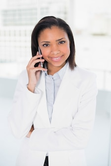 Zufriedene junge dunkelhaarige geschäftsfrau, die einen telefonanruf macht