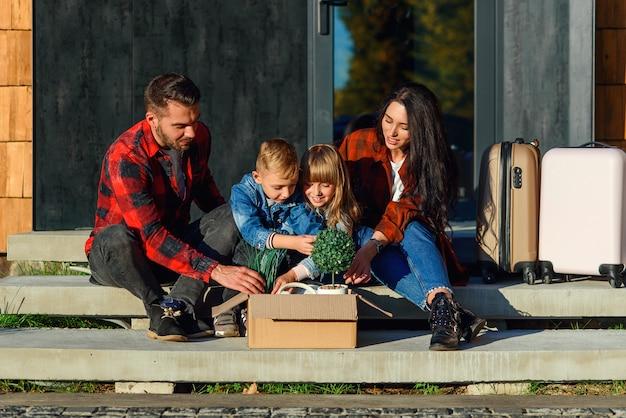 Zufriedene junge eltern mit ihren glücklichen kindern sitzen auf der treppe des neuen hauses und holen aus dem karton grüne blumentöpfe und uhr. neues stilvolles gemütliches haus der schönen familie nahe wald.