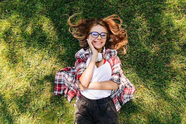 Zufriedene junge frau, die glück im park ausdrückt. überkopfporträt des reizenden mädchens, das auf grünem gras liegt.