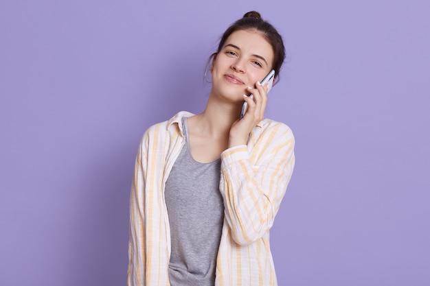 Zufriedene junge frau, die über modernes smartphone spricht