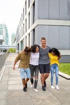 Zufriedene junge freunde, die zusammen auf straße gehen