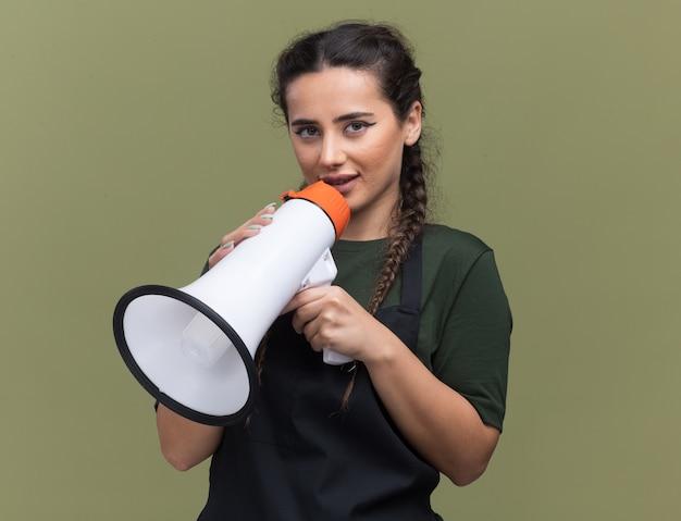 Zufriedene junge friseurin in uniform spricht über lautsprecher isoliert auf olivgrüner wand