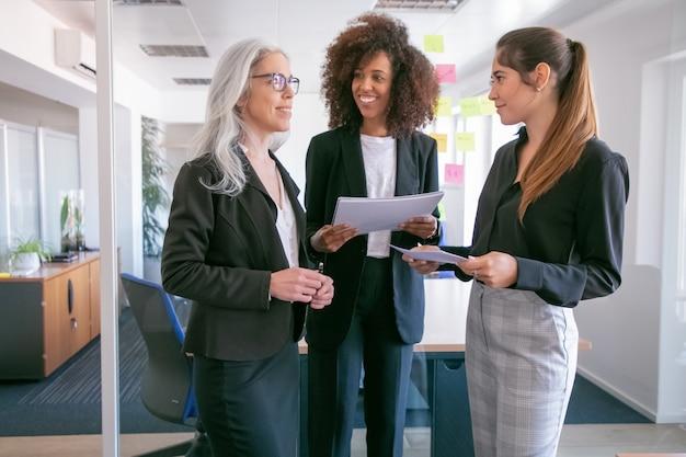 Zufriedene junge geschäftsfrauen, die statistiken diskutieren und lächeln. drei glückliche attraktive kolleginnen, die mit papieren stehen und im konferenzraum sprechen. teamwork-, geschäfts- und managementkonzept